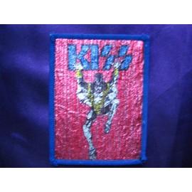 KISS Ecusson Gene Simmons sur fond rouge brillant, logo bleu
